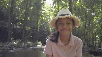 retrato linda garota com chapéu de palha está sorrindo e olhando para a câmera de vídeo enquanto está hospedado na floresta tropical durante as férias de verão. Tailândia. video