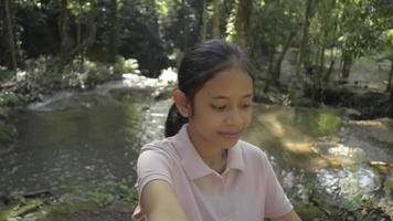 Cheerful asian female teenager wearing straw hat taking a selfie portrait while standing near the small waterfall. Cute girl having fun in tropical forest sharing selfie to friends video. video