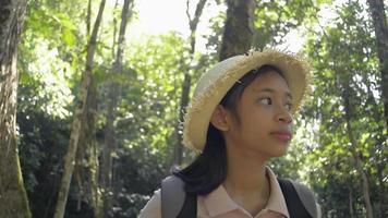 menina bonita asiática com chapéu de palha com mochila está caminhando na selva durante o acampamento de verão. conceito de experiência de viagem. video