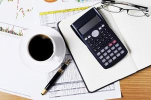 business concept with calculator and fountain pen and coffee cup on worktable with document photo