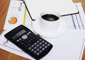 Coffee cup and calculator with blank book page on worktable with document photo
