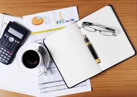 Blank business memo with eyeglasses and coffee cup and calculator and document on worktable for business concept photo