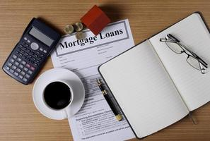 Mortgage loans concept with house paper and coins stack and coffee cup and fountain pen and calculator and eyeglasses photo