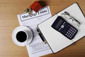 Mortgage loans concept with house paper and coins stack and coffee cup and fountain pen and calculator and eyeglasses on worktable with document photo