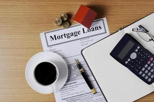 Mortgage loans concept with worktable and coffee cup and fountain pen and calculator and eyeglasses and house paper and coins stack photo