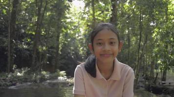 adorável garota retrato em vestido casual está sorrindo e olhando para a câmera durante o acampamento no parque florestal sa nang manora sob o sol da manhã no verão. experiência de viagem. Tailândia. video