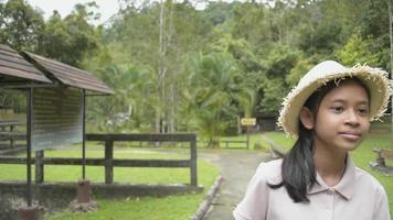 jeune fille mignonne portant un chapeau de paille marchant tranquillement et profitant de voir les beaux paysages du parc forestier pendant l'été. Thaïlande. video