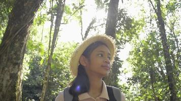 colegial usando chapéu de palha com mochila, caminhando pela floresta tropical sob a luz solar. menina bonita está caminhando na selva durante o acampamento de verão. conceito de experiência de viagem. video