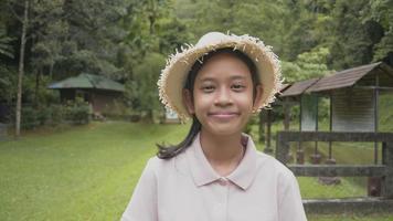 portrait de jeune fille asiatique portant un chapeau de paille souriant joyeusement dans le parc forestier. guide bénévole de jeunes femmes debout sur la pelouse pour accueillir les touristes dans la forêt tropicale. province de phang nga. Thaïlande. video