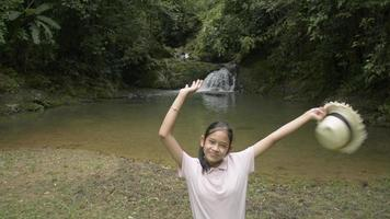 joyeuse jolie fille lève les bras en l'air avec un chapeau de paille et regarde la caméra. adolescente debout seule près d'une petite cascade dans la forêt tropicale. tir de drone aérien. video