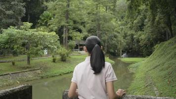 Cute asian girl enjoy watching beautiful scenery in the forest park during summer vacation. Female teenager smiling while standing near the creek in tropical forest. Thailand. video
