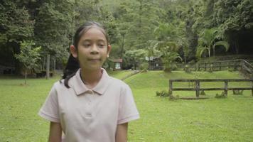 linda garota asiática caminhando vagarosamente no gramado no parque florestal durante as férias de verão. adolescente feminino feliz sorrindo durante a observação da paisagem da floresta tropical. Tailândia. video