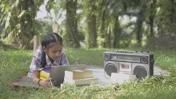Cute girl using digital tablet with social media online while laying on the mat in the grass field. Adorable female teenager doing homework and listening music from old vintage radio device. video