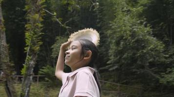 tournant autour d'une joyeuse fille asiatique portant un chapeau de paille regardant autour d'un parc forestier à feuillage luxuriant. vacances d'été. voyage d'excursion. Thaïlande. video