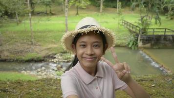 Happy asian female teenager wearing straw hat taking a selfie portrait while standing near the creek at forest park. Cute girl having fun in public park sharing selfie to friends video. video