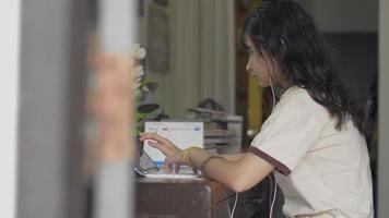 enthülle erschossenes Universitätsmädchen mit Kopfhörer mit digitalem Tablet-Touchscreen auf dem Schreibtisch für das Online-Studium zu Hause. Social-Media-Kommunikation. video