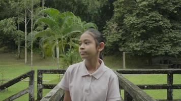 jolie fille asiatique marchant tranquillement sur le vieux pont en béton dans le parc forestier pendant les vacances d'été. heureuse adolescente regardant les paysages de la forêt tropicale. Thaïlande. video