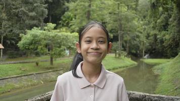 portrait jolie fille asiatique sourit en se tenant debout sur le déversoir au-dessus du canal dans le parc forestier. adolescente regardant la caméra vidéo avec bonheur dans la forêt tropicale. Thaïlande. video