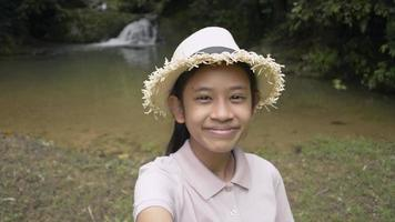 Happy asian female teenager wearing straw hat smiling and taking a selfie portrait while standing near the small waterfall. Pretty girl having fun in tropical forest sharing selfie to friends video. video
