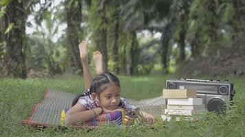 Adorable girl enjoy using mobile phone with earphone while laying on the mat in the park. Relax female teenager watching lesson online from smartphone during study at home. Education. video