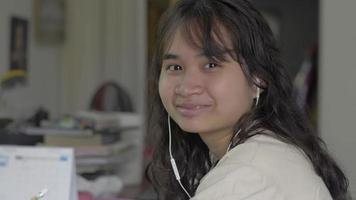Close up portrait asian university girl wearing earphone smiling happily at the desk at home. Study at home. Lesson online. Distance education concept. video