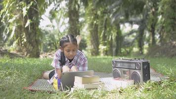 Adorable girl using digital tablet on the grass field. Female teenager laying on the mat among oil palm under sunlight. Relaxing while reading and listening during doing homework in the park. video