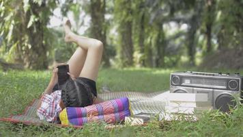 Relax girl laying on the mat while using mobile phone happily in the park. Female teenager enjoy listening music from old vintage radio device in the lawn. Hobbies and Leisure. video