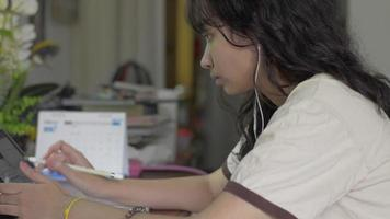Close up asian female teenager writing on digital tablet at the desk for lesson online at home. University girl in casual dress with earphone doing homework on the table. Study of the exam. video