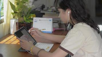 Asian female teenager sitting and using digital tablet on the desk for lesson online at home. University girl in casual dress with earphone doing homework on the table. Writing on digital device. video