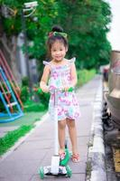Cute little asian girl learning to ride a scooter on footpath photo