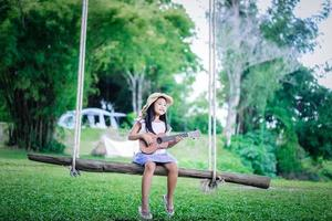 Little asian girl sitting on wooden swing playing ukulele while camping in nature park photo