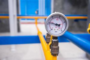 Closeup of manometer for measuring gas pressure. Pipes and valves at industrial plant photo