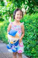 Portrait of happy asian little girl with doll standing on footpath in the park photo