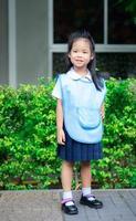 Portrait of happy little girl in Thai school uniform standing on footpath, ready back to school photo