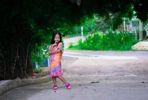 Portrait of happy asian little girl in dress standing on footpath in the park photo