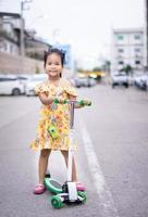 Cute little asian girl in yellow dress playing a scooter on street photo