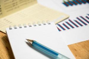 Fondo de libreta, cuaderno con bolígrafo y gráfico financiero. foto