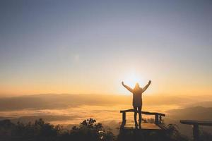 Man rise hand up on top of mountain and sunset,  Freedom and travel adventure concept. Religious beliefs, Copy space. photo