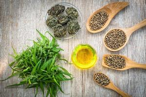 Hemp oil and hemp seeds on a wooden table, Medical marijuana products including cannabis leaf, cbd and hash oil, alternative remedy or medication,medicine concept. photo