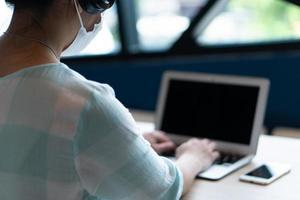 Joven asiática con mascarilla y auriculares y usando la computadora para trabajar desde casa durante el brote de covid-19 o coronavirus. distanciamiento social y nuevo concepto de estilo de vida normal foto