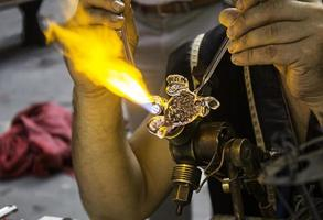 Artisan blowing glass in a traditional way photo