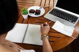 Mujer mayor escribiendo un diario en la mesa durante el brote de covid 19 foto