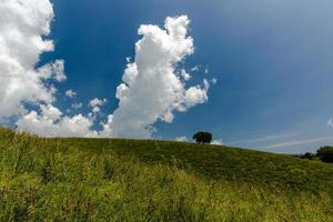 Blue sky and green hill photo
