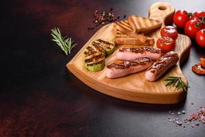 Tasty, fresh sausages grilled with vegetables spices and herbs photo