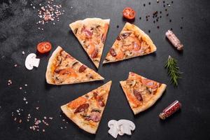 deliciosa pizza fresca hecha en un horno de hogar con tomates, salchichas y champiñones foto