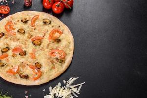 Fresh delicious pizza made in a hearth oven with shrimp mussels and other seafood photo