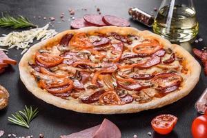deliciosa pizza fresca hecha en un horno de solera con salchicha, pimiento y tomates foto