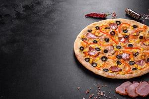 deliciosa pizza fresca hecha en un horno con aceitunas, ají y jamón foto