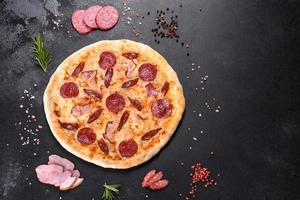 deliciosa pizza fresca hecha en un horno de hogar con cuatro tipos de carne y salchicha foto