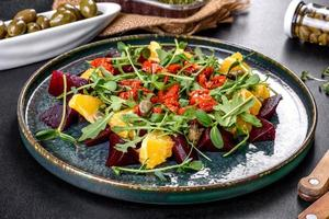 Tasty fresh healthy salad with boiled beets, microgreen and orange photo
